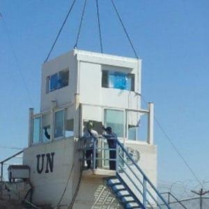 既存監視ポストに向かってクレーンに吊り下げられる要塞化シェル